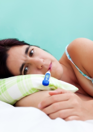 Beautiful hispanic woman sick in bed with a thermometer in her mouth photo
