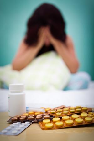 enfermedades mentales: Tabletas de médicos en el primer plano con un cabo de la mujer se centran en el fondo que sufre de depresión o dolor de cabeza