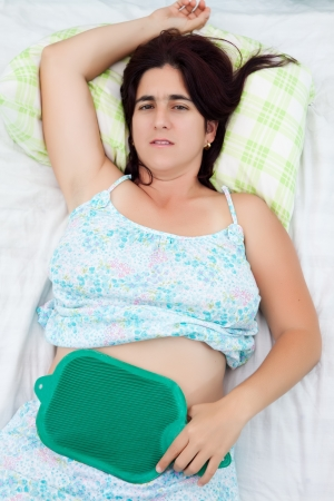 menstrual: Young woman suffering from abdominal or menstrual pain laying in bed with a plastic hot water bottle Stock Photo