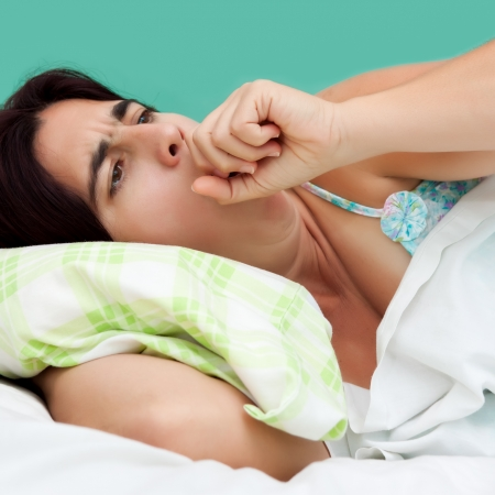 coughing: Close-up portrait of an hispanic woman coughing and resting in a bed