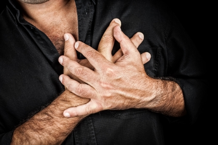 infarction: Close up of two hands grabbing a chest on a black background, useful to represent a heart attack or any sentimental concept