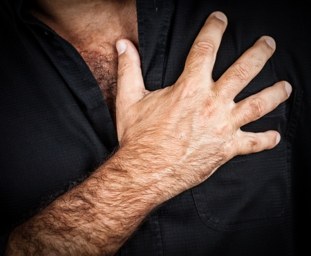 palpitation: Close up of a hand grabbing a chest on a black background, useful to represent a heart attack or any sentimental concept