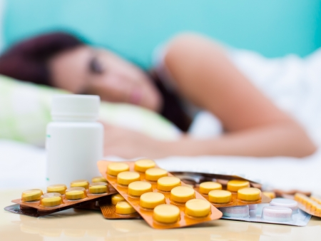 Out of focus woman resting in bed with some pills from her medical treatment on a table in the foreground photo