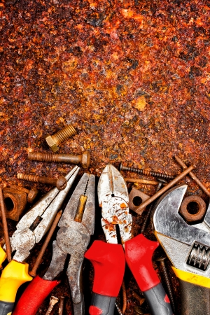 Vertical shot of a set of tools, nuts and bolts  on a rusty metallic background with space for text photo