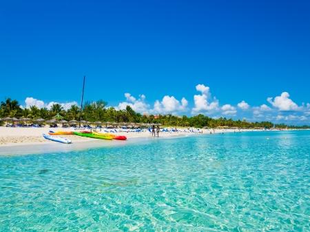 Der schöne Strand von Varadero in Kuba mit bunten Booten und strohgedeckten Sonnenschirmen Bild aus dem Meer entnommen