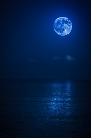 Bright full moon with reflections on a calm ocean at midnight photo