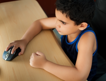 Small hispanic boy working on a computer or browsing the web at home photographed from above photo