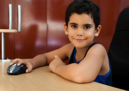 niños latinos: Lindo niño hispano de pequeña a trabajar en un ordenador en casa y sonriendo