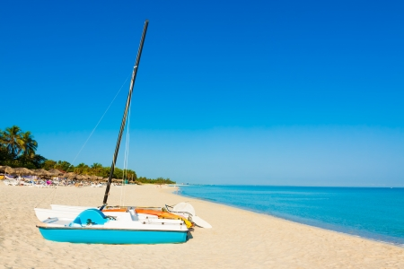 Sailing boats and thatched umbrellas on the  beach of Varadero in Cuba on a beautiful  summer day photo