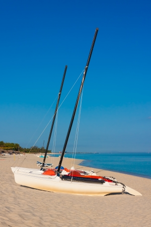 Sailing boats at a deserted beach in Cuba on a beautiful summer morning photo