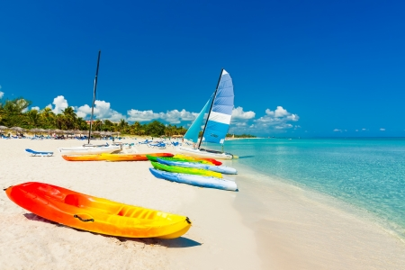 Colorful kayaks and sailing boats on a tropical beach in Cuba photo