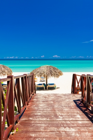 Walkway leading from a resort to a tropical beach in Cuba on a beautiful summer day photo