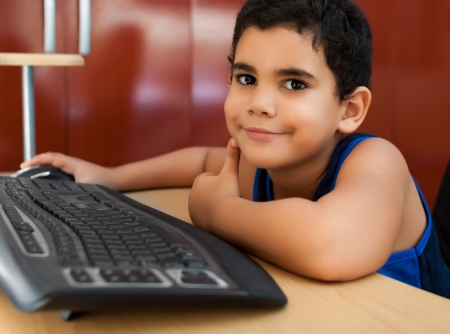 working on school project: Happy hispanic child working with a computer on his bedroom and smiling Stock Photo