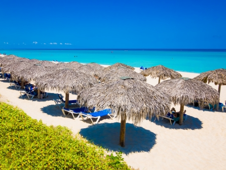 Row of thatched umbrellas at the famous Varadero beach in Cuba on a beautiful summer day photo