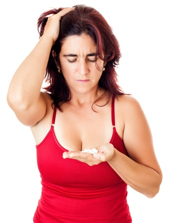 Hispanic woman  with a sad expression looking at a lot of medicine pills she is holding on her hand useful to illustrate mental health issues, drug addiction or suicide photo