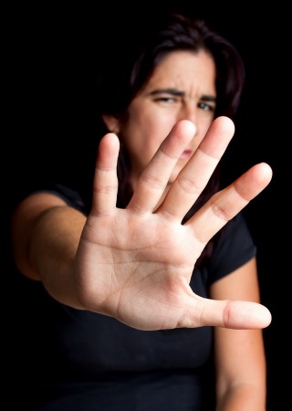 Frightened woman with her hand extended trying to stop any coming danger on a black background photo