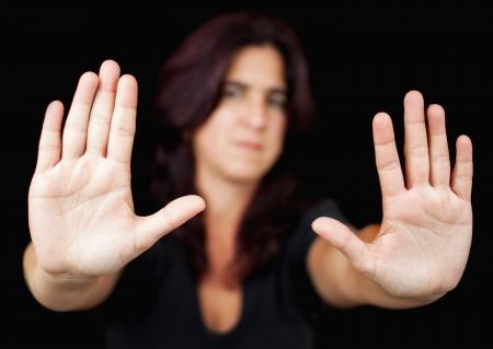 signalering: Onscherp vrouw met haar handen signalering naar geïsoleerd te stoppen op een zwarte achtergrond Stockfoto