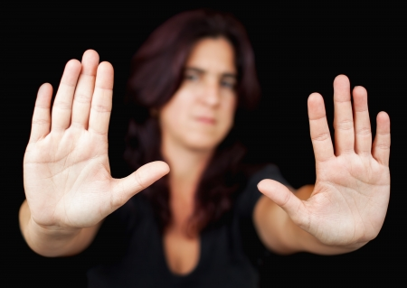 struggling: Out of focus woman with her hands signaling to stop isolated on a black background Stock Photo