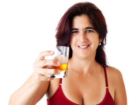Beautiful hispanic woman in her thirties with a glass of whisky, rum  or any other golden liquor isolated on white photo