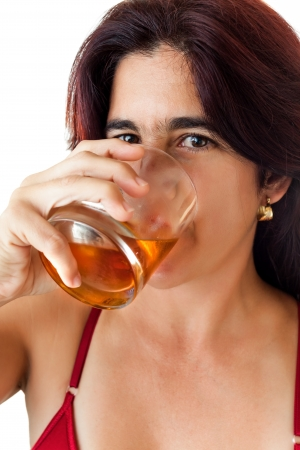 Beautiful hispanic woman in her thirties drinking whisky, rum or any other golden liquor isolated on white photo