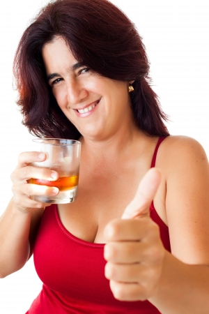 Beautiful hispanic woman in her thirties drinking whisky, rum or any other golden liquor and doing a thumbs up sign isolated on white photo