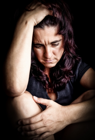 sad face: Woman suffering from a very strong depression with a very sad face on a black background Stock Photo