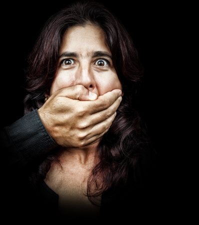 dictatorship: Dark portrait of a woman being abused and silenced by a man who is covering her mouth with his hand Stock Photo