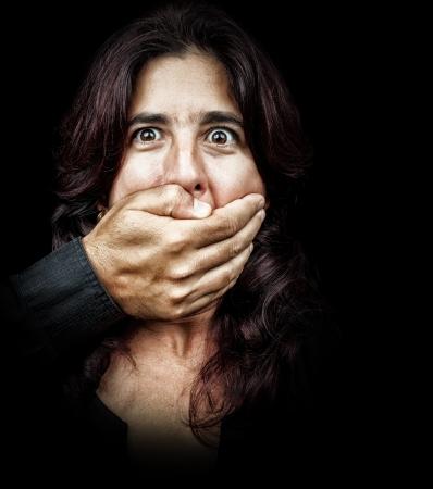 discriminacion: Oscuro retrato de una mujer víctima de abuso y silenciado por un hombre que se tapaba la boca con la mano Foto de archivo