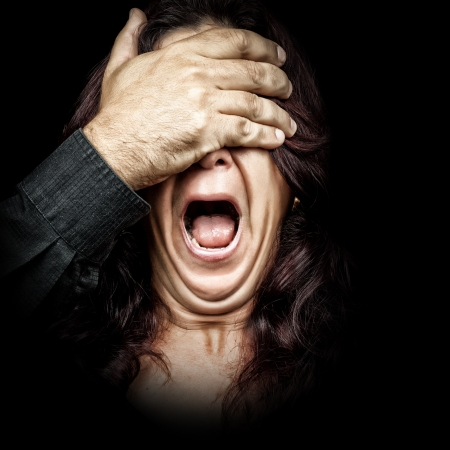 abused women: Dark portrait of a woman being abused and silenced by a man who is covering her eyes with his hand while she screams