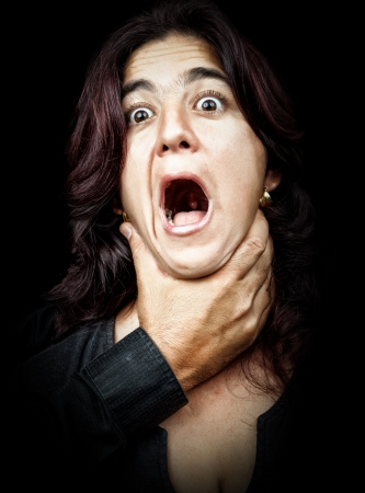 Dark portrait of a woman being abused and strangled by a man while she screams Stock Photo - 14309858