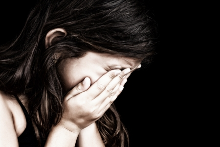 Dramatic grunge portrait of a girl crying with her hands on her face isolated on a black background photo