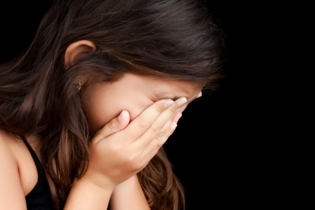 is embarrassed: Dramatic portrait of a girl crying with her hands on her face isolated on a black background