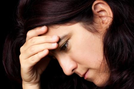 illnesses: Dram�tico retrato de una mujer muy estresada hispanos que sufren de depresi�n o dolor de cabeza aislado en un fondo negro