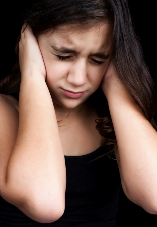 Dramatic portrait of a frightened girl with a very emotional expression isolated on a black background photo