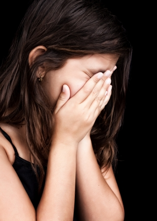 niño llorando: Retrato lateral de una hermosa niña llorando y tapándose la cara aislada en negro Foto de archivo