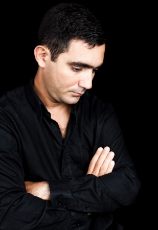 Hispanic man with a sad and thoughtful expression standing isolated on a black background photo