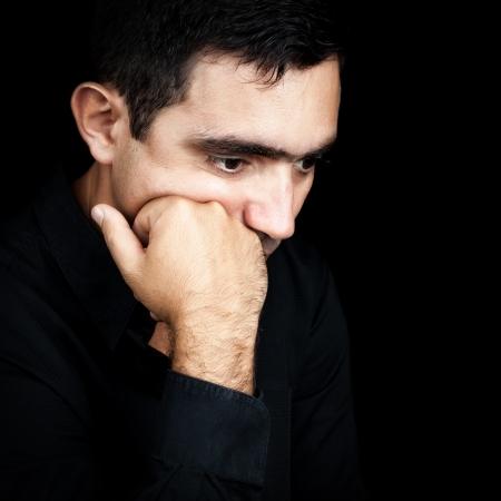 homme inquiet: Close-up portrait d'un homme hispanique beau penser avec un coup de poing sur le menton isol� sur noir Banque d'images