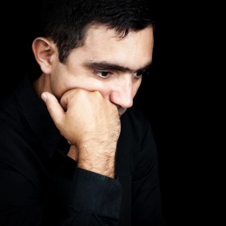 Close-up portrait of a handsome  hispanic man thinking with a fist on his chin isolated on black