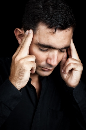 Dramatic portrait of an hispanic man suffering from depression or a strong headache isolated on black Stock Photo