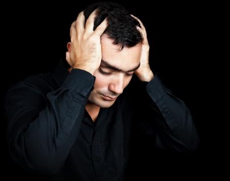 hombre preocupado: Cl�sico retrato de un hombre hispano de sufrir un fuerte dolor de cabeza o depresi�n presionando la frente con las manos aisladas en negro