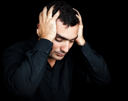 migraine: Classic portrait of an hispanic man suffering a strong headache or depression pressing his forehead with his hands isolated on black Stock Photo