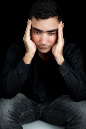 Classic portrait of an hispanic man suffering a strong headache or depression pressing his forehead with his hands isolated on black photo