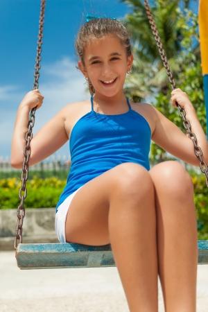 Beautiful hispanic girl riding a swing outdoors at an amusement park photo