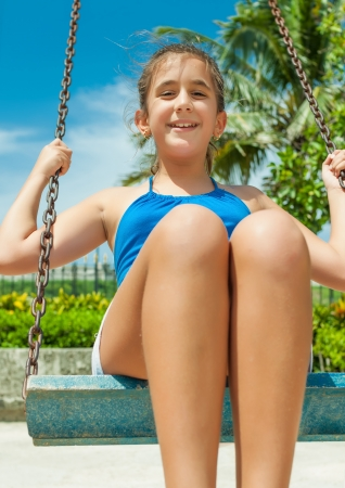 Beautiful hispanic girl riding a swing outdoors at an amusement park photo