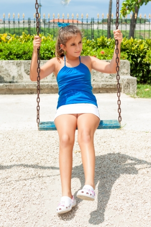 preteen: Beautiful hispanic girl riding a swing outdoors at an amusement park