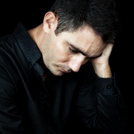wanhopig: Dramatische close-up van een bezorgde en depressieve man geïsoleerd op zwart Stockfoto