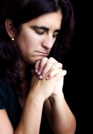 suffering: Hispanic woman praying with a sad face isolated on black