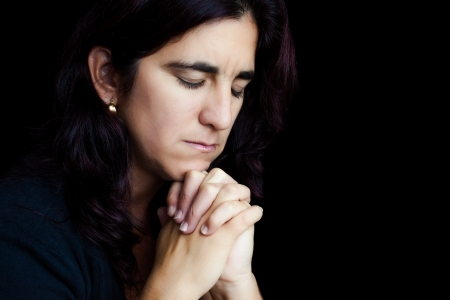 woman praying: Dramatic portrait of an hispanic woman praying isolated on black with space for text