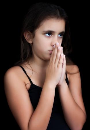 Young hispanic girl praying isolated on black photo