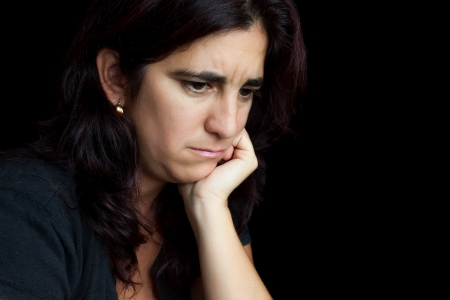depressed girl: Portrait of a sad and depressed hispanic woman with a thoughtful expression isolated on black Stock Photo